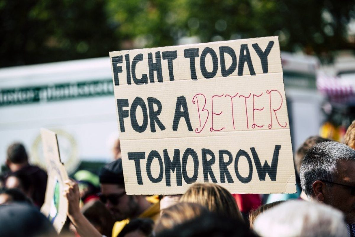 Woman Holding Sign That Reads: Fight Today For A Better Tommorow